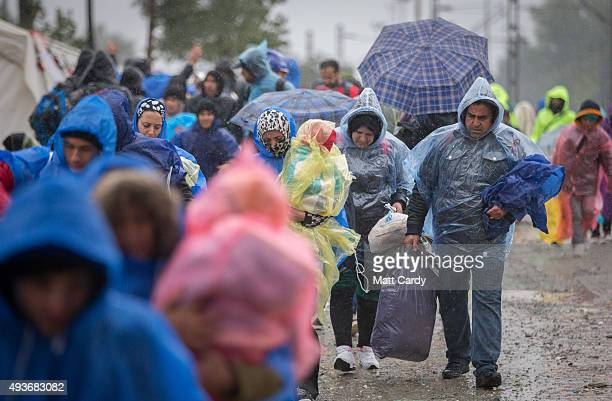 Migrants walk carrying their belongings in the rain as they head towards the Macedonian border at a refugee transit camp that has been set up on the...