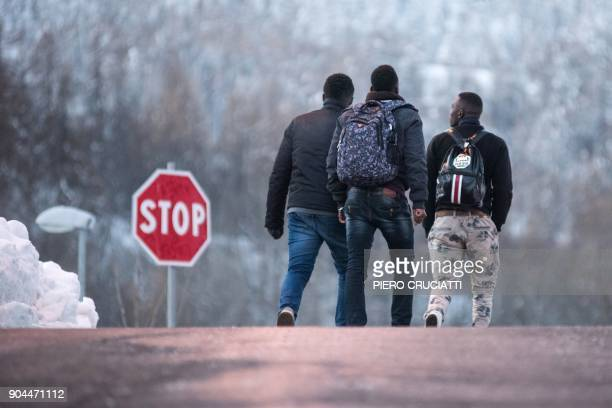 Migrants walk in direction of the Colle della scala a snowcovered pass to cross the border between Italy and France on January 13 2018 near...