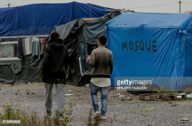 TOPSHOT Migrants walk in the 'Jungle' migrant camp in Calais northern France on November 1 a day after a massive operation to clear the squalid...