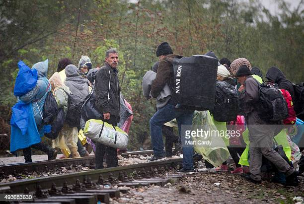Migrants walk in the rain along the tracks as they cross into Macedonia as they leave a refugee transit camp that has been set up on the border of...