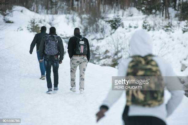 Migrants walk in the snow on their way to the Colle della Scala a snowcovered pass to cross the border between Italy and France on January 13 2018...