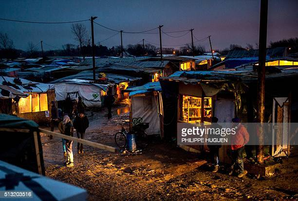 TOPSHOT Migrants walk in the southern part of the socalled 'Jungle' migrant camp while half of the camp is being dismantled in the French northern...
