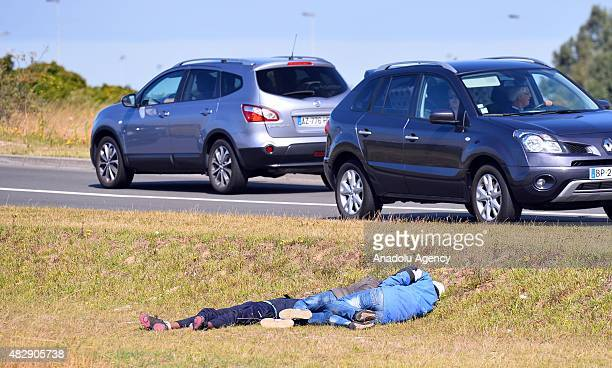 Migrants walk next to a road as they try to access train tracks which lead to the Channel Tunnel in Calais France on August 4 2015 More than 2...