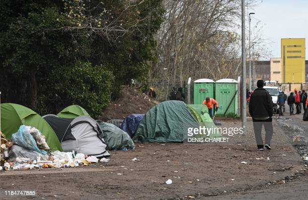 Migrants walk next to makeshift tents set up at a camp in Calais, northern France, on Novenber 26, 2019.