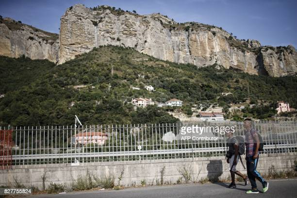 Migrants walk next to the Roya River on August 8 2017 in Ventimiglia close to the French border / AFP PHOTO / Marco BERTORELLO
