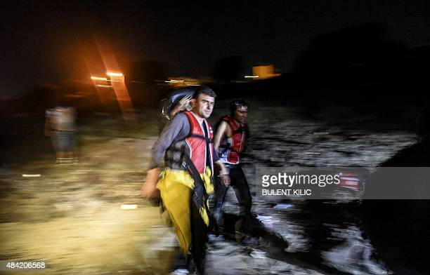 Migrants walk on the beach to board a boat to the Greek island of Kos on early August 16 2015 off the shore of Bodrum southwest Turkey Authorities on...