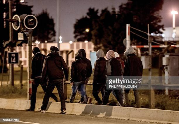 Migrants walk out of the 'Jungle' to reach the circular road to block trucks passing by in order to get inside and travel to Great Britain in Calais...