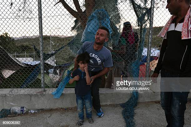 Migrants walk out through a hole in the Moria camp on the island of Lesvos on September 20, 2016. Thousands of migrants were forced to flee to safety...