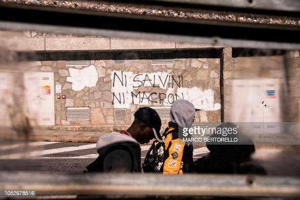 Migrants walk past an inscription reading in French Neither Salvini nor Macron on October 21 2018 in the Alpine border town of Claviere some 100...