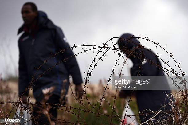 Migrants walk past barbed wire fences at the Temporary Permanence Centre on February 19 2015 in Lampedusa Italy Hundreds of migrants have recently...