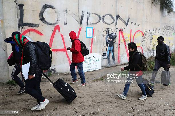 Migrants walk past 'London Calling' graffiti as they begin to leave the Jungle migrant camp in the early morning before authorities demolish the site...