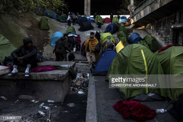 Migrants walk past remaining tents as police officers and security agents carry out an evacuation of a makeshift camp at Porte de la Chapelle in the...