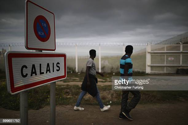 Migrants walk past secuirty fencing at the Jungle migrant camp on September 6 2016 in Calais France The dropin cafe for children is still facing...
