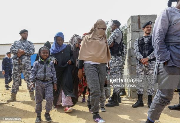 Migrants walk past security forces as they prepare to meet United Nations SecretaryGeneral Antonio Guterres during his visit to Ain Zara detention...