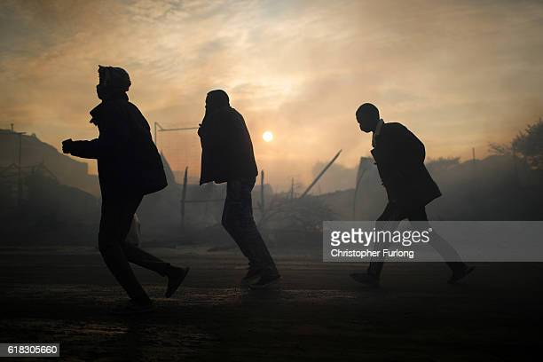 Migrants walk through the burnt out Jungle camp as authorities demolish the site on October 26 2016 in Calais France Overnight fires broke out in...