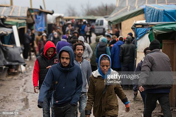 Migrants walk through the camp known as 'The Jungle' on January 5 2016 in Calais France Thousands of migrants continue to live in the makeshift camp...
