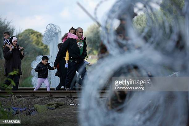 Migrants walk through the gap in the razor wire fence at the Hungarian border with Serbia on September 12 2015 in Roszke Hungary Migrants are rushing...