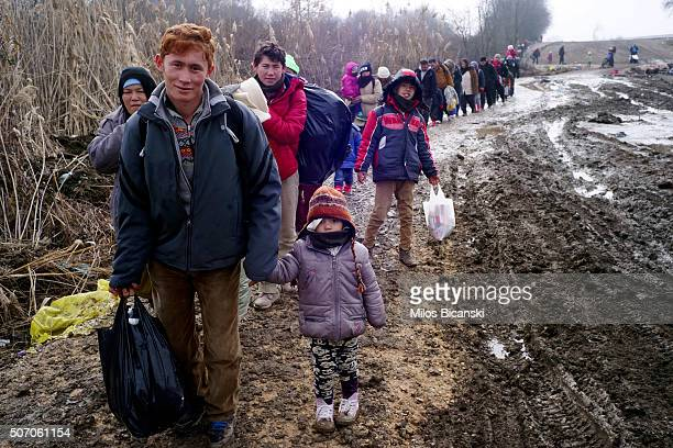 Migrants walk through thick mud as they cross the Macedonia / Serbia border in the southern Serbian village of Miratovac on January 27, 2016 in...