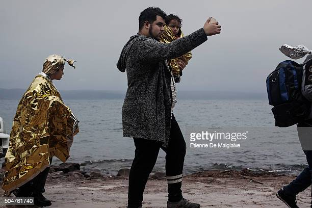 Migrants walk to a transit camp after they landed on a rubber boat Refugees from Afghanistan and Syria arrive in boats on the shores of Lesbos near...