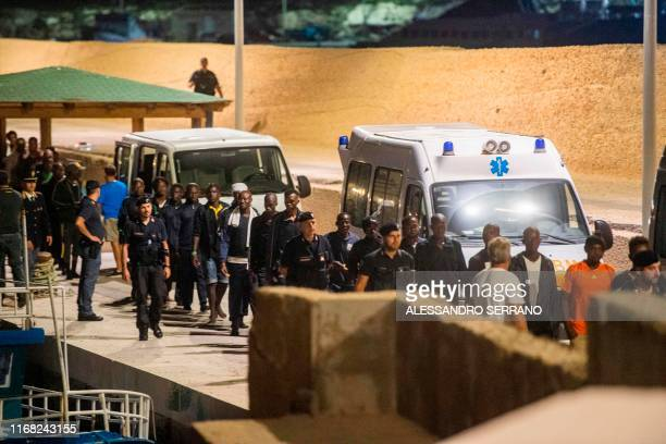 Migrants walk to board vans after being rescued by the Ocean Viking rescue ship and disembarking on Italy's southern island of Lampedusa in the...