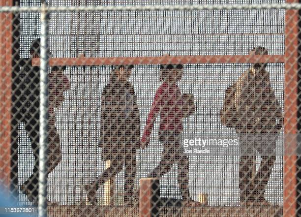 Migrants walk together along the US/Mexican border wall as they look to turn themselves over to the US Border Patrol as they seek asylum in the...
