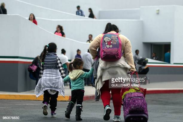 Migrants walk towards El Chaparral port of entry in Tijuana Mexico in the boder with the United States on June 21 2018 US lawmakers were poised to...