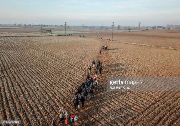 Migrants walk towards Greece along the Turkey-Greece border near Pazarkule, in Edirne district, on March 1, 2020. - Turkey will no longer close its...