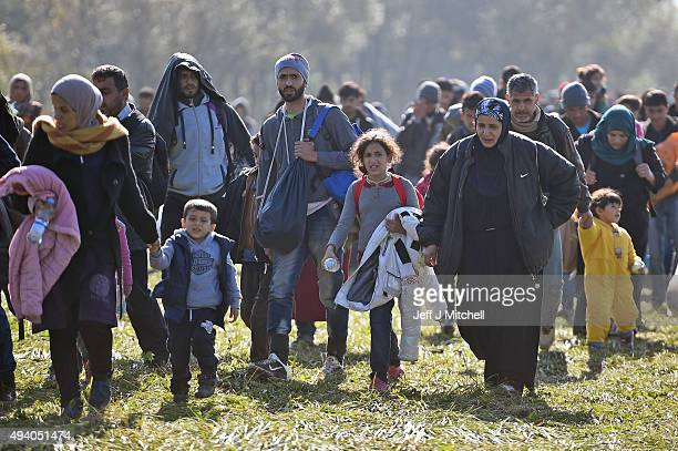 Migrants walk towards the village of Rigonce, after crossing over from Croatia on October 24, 2015 in Rigonce, Slovenia. Thousands of migrants...