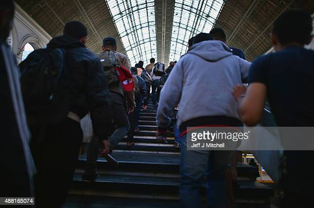 Migrants walk up the stairs as they prepare to board a train leaving for the Austrian border at the Keleti railway station on September 14 2015 in...