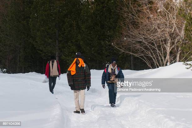 Migrants walks to reach another village after crossing the French border on December 22 2017 in Bardonecchia Turin Italy After the police reinforced...