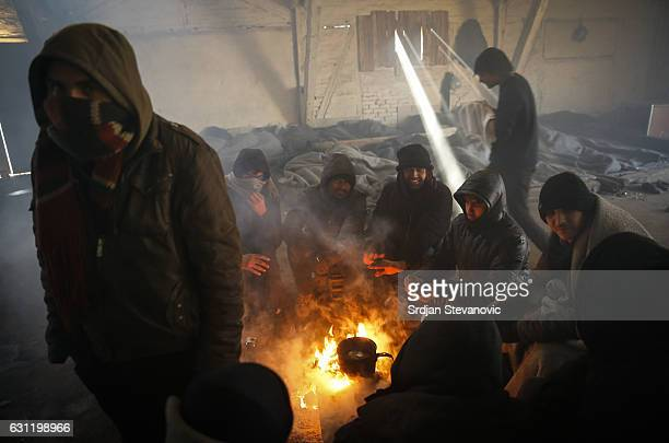 Migrants warm themselves by the fire inside a derelict customs warehouse on January 7 2017 in Belgrade Serbia Yesterday temperatures dropped to as...