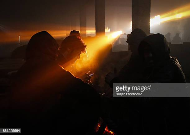 Migrants warm themselves by the fire inside a derelict customs warehouse on January 8 2017 in Belgrade Serbia Today temperatures dropped to as low as...