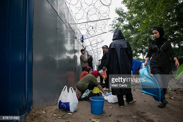 Migrants wash their clothes using the single tap that has been provided besides the border fence close to the E75 Horgas border crossing between...