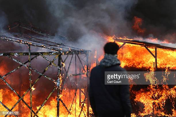 Migrants watch a hut burn as police officers clear part of the 'jungle' migrant camp on February 29 2016 in Calais France The French authorities have...