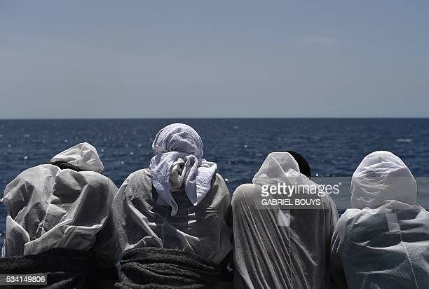 Migrants watch the sea from the rescue ship 'Aquarius' on May 25 2016 a day after a rescue operation of migrants and refugees off the Libyan coast...