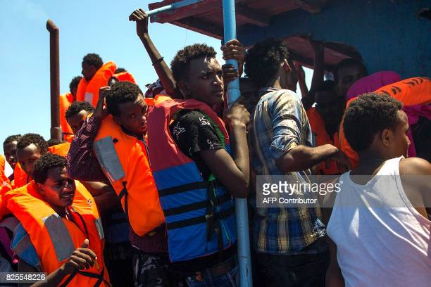 Migrants wearing life jackets wait to be rescued by the Aquarius rescue ship run by nongovernmental organisations 'SOS Mediterranee' and 'Medecins...