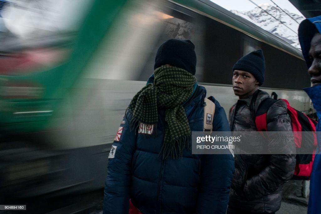 Migrants wearing warm clothes wait at the station as a train approaches the platform in Bardonecchia, on January 13, 2018. Migrants are now trying to reach France crossing the Italian Alps by the snow-covered pass Colle della Scala (Col de l'Echelle) despite snow and bad weather conditions. / AFP PHOTO / Piero CRUCIATTI