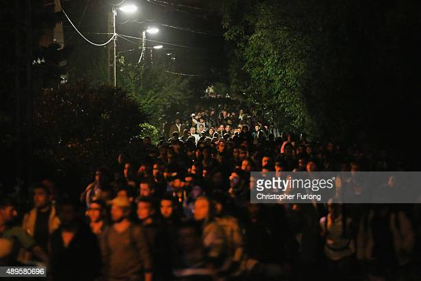 Migrants who arrived on the third train today at Hegyeshalom on the Hungarian and Austrian border walk the four kilometres into Austria on September...