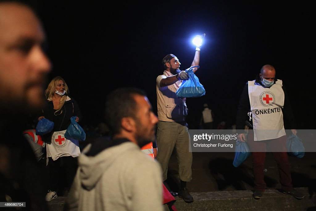 Migrants who arrived on the third train today, at Hegyeshalom on the Hungarian and Austrian border, are given food by volunteers as they walk the four kilometres into Austria on September 22, 2015 in Hegyeshalom, Hungary. Thousands of migrants have arrived in Austria over the weekend with more en-route from Hungary, Croatia and Slovenia. Politicians across the European Union are holding meetings on the refugee crisis with EU leaders attending an extraordinary summit on Wednesday to try and solve the crisis and the dispute of how to relocate 120,000 migrants aross EU states.