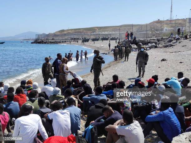 Migrants who arrived swimming to Spanish territory of Ceuta are seen as Spanish soldiers stand guard, on May 18, 2021. Starting on Monday, an...
