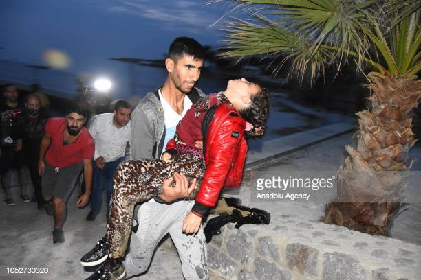 migrants who escaped drowning are being taken to ambulances as Turkish Coast Guard conduct a search and rescue operation after a boat carrying...