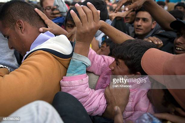 Migrants who had crossed the Serbian border into Hungary fight to get on a bus taking people to a refugee camp on September 8 2015 in Morahalom...