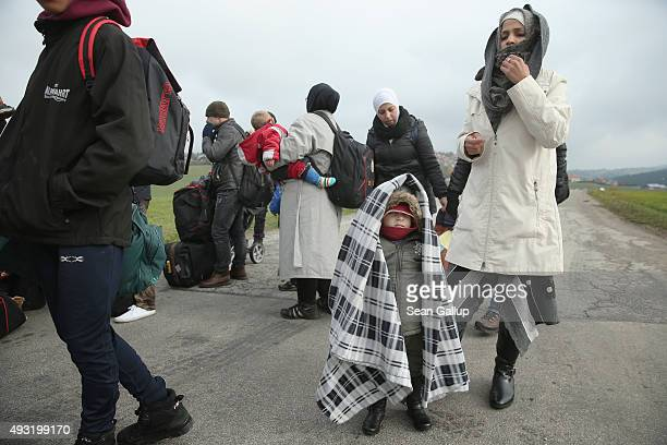 Migrants who had walked across the nearby border from Austria arrive at a temporary police facility on October 17 2015 in Wegscheid Germany According...