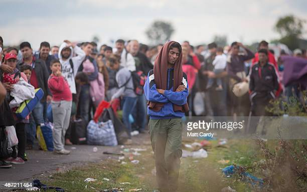Migrants who have just crossed into Hungary wait for buses to take them to a reception camp on September 7 2015 in Roszke Hungary As the migrant...