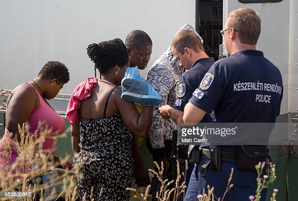 Migrants who have just crossed the border from Serbia into Hungary board a bus organised by the police to take them to the nearby Roszke transit...