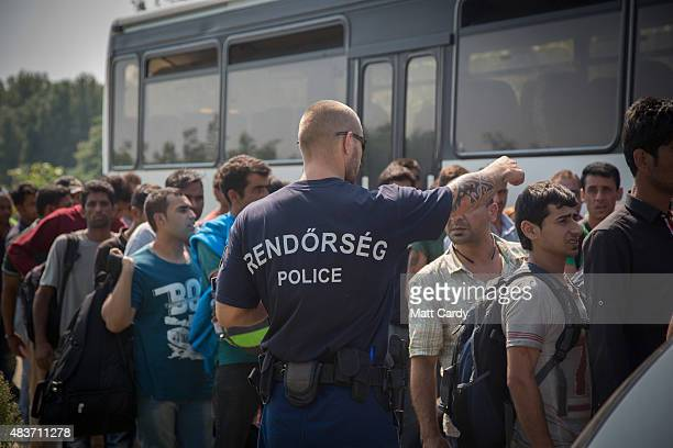 Migrants who have just crossed the border from Serbia into Hungary queue to board a bus organised by the police to take to them to the nearby Roszke...