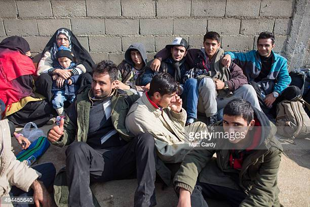 Migrants who have just crossed the border with Macedonia sit in a queue as they wait to catch a bus that will take them to a registration centre in...