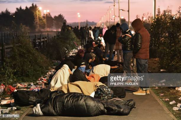 TOPSHOT Migrants who slept outside an aid station queue to be assigned to one of the processing centres across France near the 'Jungle' migrant camp...