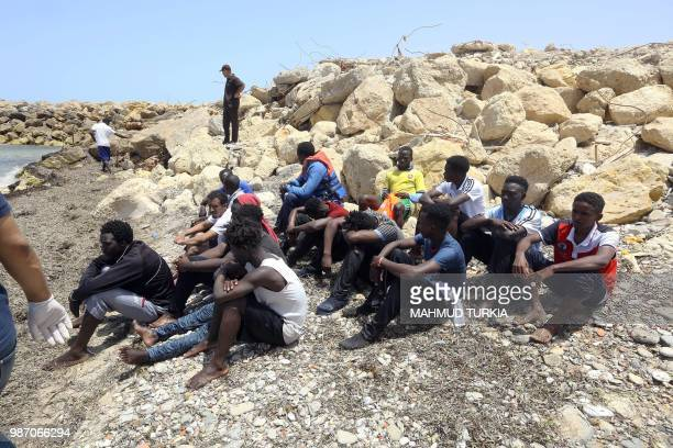 TOPSHOT Migrants who survived the sinking of an inflatable dinghy boat off of the coast of Libya are grouped on the shore of alHmidiya east of the...