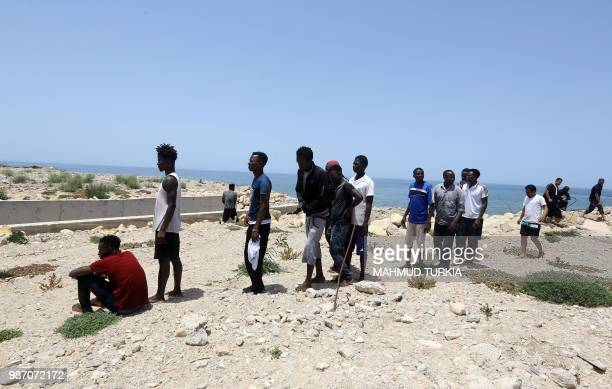Migrants who survived the sinking of an inflatable dinghy boat off of the coast of Libya arrive on the shore of alHmidiya east of the capital Tripoli...
